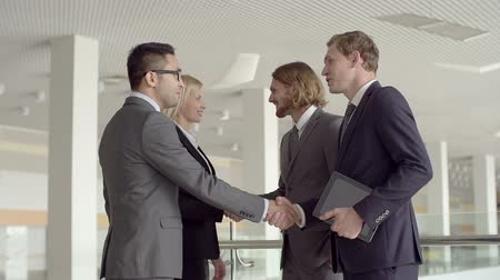 képviselő : Slow motion of four business partners meeting and shaking hands