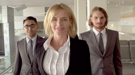 lobi : Slow-motion of smiley blond woman walking towards camera, her male colleagues following her