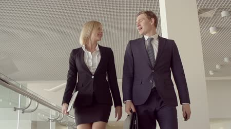 полет : Low angle of blond lady and her business partner walking towards camera and communicating in slow motion Стоковые видеозаписи