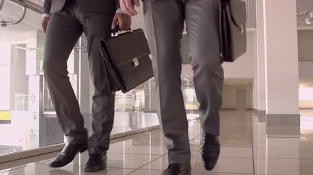 Tilt up from shoes to faces of officially dressed guys walking towards camera with briefcases in slow motion