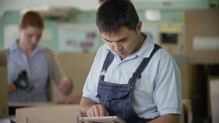 устройство : Tilt of man in dungarees browsing pad, his colleagues in background
