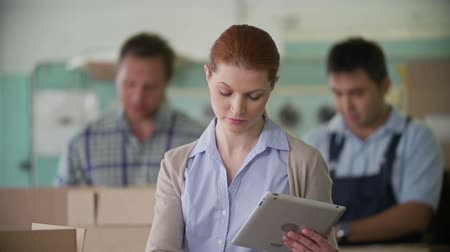 накладные расходы : Tilt of business lady crosschecking printed produce with data on screen of portable computer