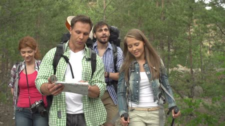 направлять : Two camping couples approaching camera in slow motion, searching their way through the woods, consulting map and compass