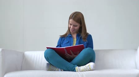 personalidade : Young girl sitting on sofa cross-legged and making some notes