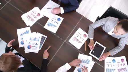 analyzovat : High angle panning shot of people at business meeting with graphic documents