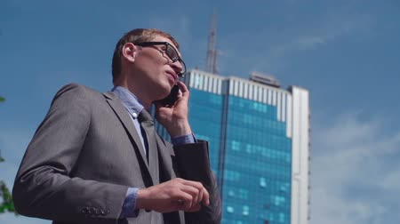 telekomünikasyon : Low angled shot of speccy businessman making a call outdoors Stok Video