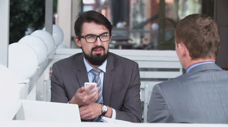 corporate affairs : Two businessmen in street restaurant discussing affairs Stock Footage