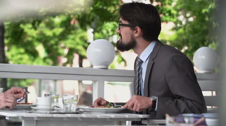 ábrázol : Two business men having meal at pavement café during negotiations