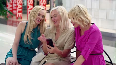 bestie : Chicks taking break from shopping rush surfing the net  Stock Footage