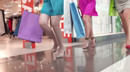 butik : Low angle of unrecognizable girls running with shopping bags on high heels in slow motion