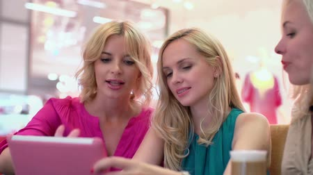 pesquisa : Three friends shopping online sitting at table in cafe