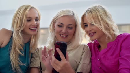 mainstream : Three blondes having fun with smartphone Stock Footage