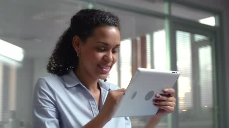 mainstream : Cheerful white-collar worker with dark complexion browsing digital tablet