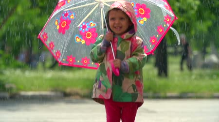 wallow : Cute baby bouncing with umbrella in rainfall Stock Footage