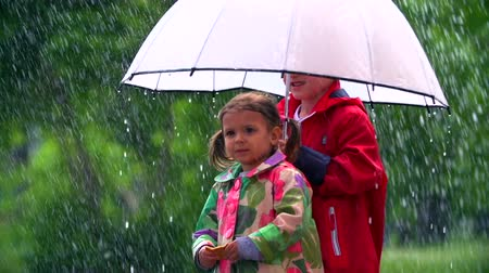 сестра : Kids standing with umbrella under pouring rain Стоковые видеозаписи