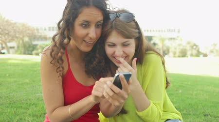 тыкать : Two girls laughing at something on the screen of the phone Стоковые видеозаписи
