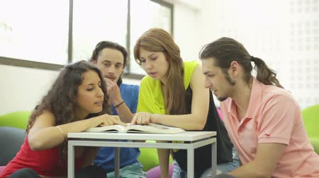ponto de referência : Four students looking up information in a huge book Stock Footage
