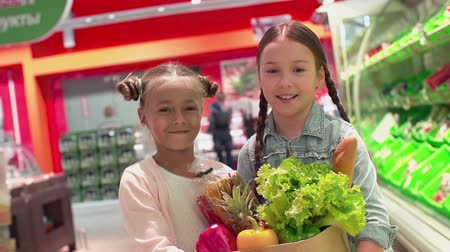grocery : Close up of two kids approaching camera with bag stuffed with food in slow motion and looking straight into camera
