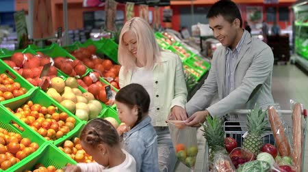 покупка товаров : Family enjoying grocery shopping, selecting tangerines together