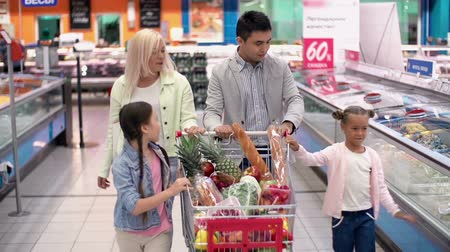 покупка товаров : Pull back of family in supermarket strolling with shopping trolley full of products joyfully chatting