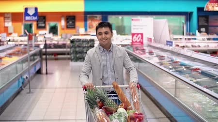 kordé : Guy with full supermarket trolley approaching camera and smiling happily Stock mozgókép