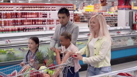 супермаркет : Tracking shot of family of four walking along supermarket rows with shopping cart in slow motion