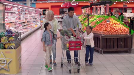 grocery : Slow motion of family walking leisurely along supermarket rows and having a lot of fun
