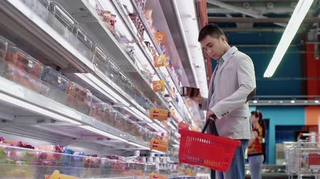 продукты : Low angle of guy shopping in dairy products department Стоковые видеозаписи