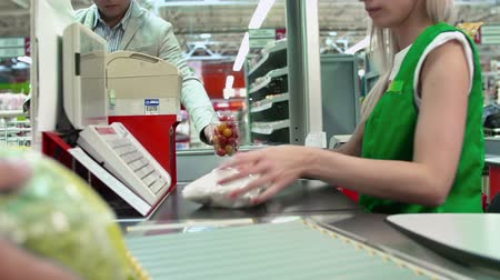 регистр : Close up of check till and products on conveyor belt, people are unrecognizable