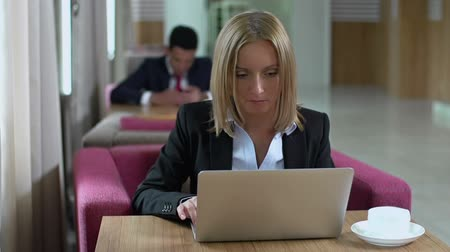 vago : Businesswoman working at laptop in waiting room, squinting and narrowing her eyes, man in formalwear in the background