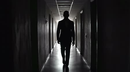 isolar : Shaky shot of man hastily approaching camera along the narrow dark passageway Stock Footage