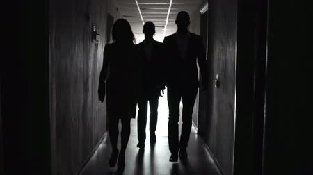 épico : Group of people approaching camera in the dark hallway