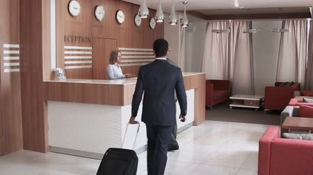 отель : Long shot of auburn-haired man checking in at the reception desk, another man with luggage bag arriving
