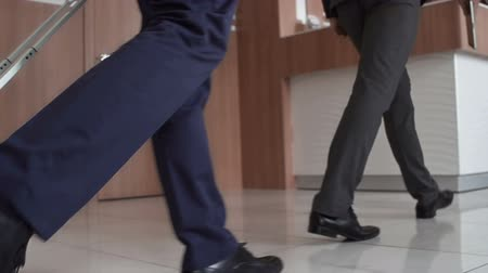 viagens de negócios : Low angled tracking shot of male feet with luggage coming up to the reception desk, tilted up so that faces are seen