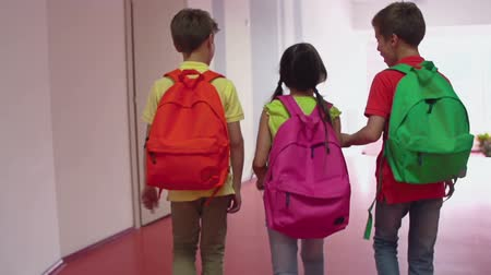 walk behind : Camera following three kids with backpacks walking along the school passageway during recess