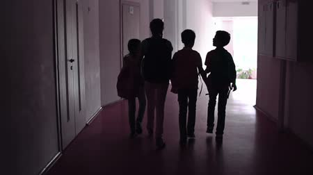 walk behind : Camera following four outlines of schoolchildren passing through the dark hallway in slow motion