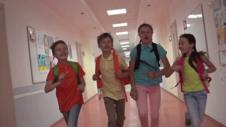 birincil : Four blissful pupils running through school corridor, approaching camera in slow motion