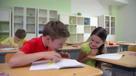 tricky : Dolly of two classmates whispering at lesson Stock Footage