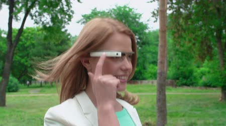 espetáculos : Tracking shot of lady scrolling and swiping google glass on her way through the park