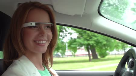 espetáculos : Pretty lady with toothy smile using smart glasses while driving a car