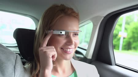 latest : Close up of girl sitting on back seat of car and using wearable computing device