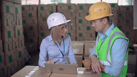 распределение : Dolly in of supervisor giving verbal reprimand to the laborer in warehouse