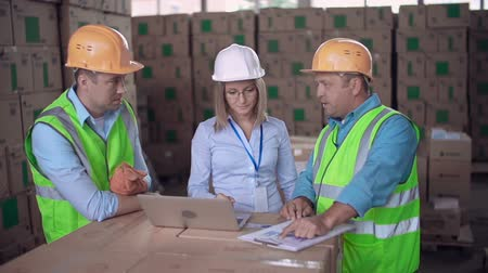 Close up of three workers comparing digital data and printed documentation in warehouse