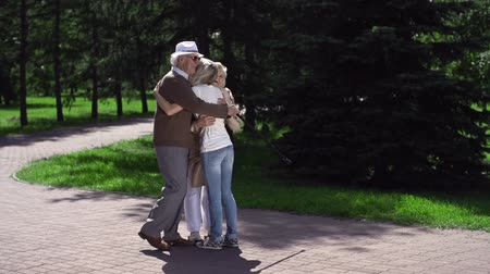 parentes : Granddaughter meeting her grandparents and greeting them with a sentimental squeeze