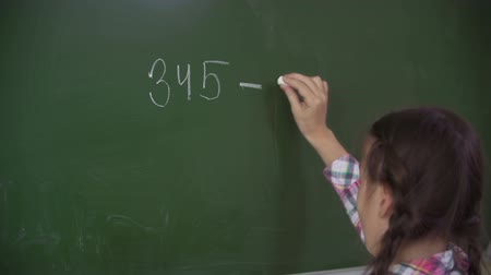 tizenéves lányok : Girl at the green board subtracting 230 from 345