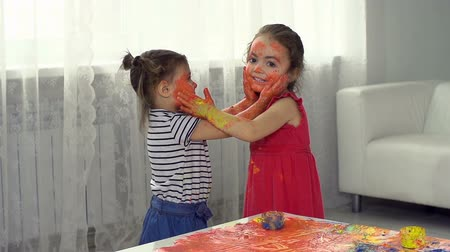 nepořádek : Two little girl friends smearing paint on each other's face