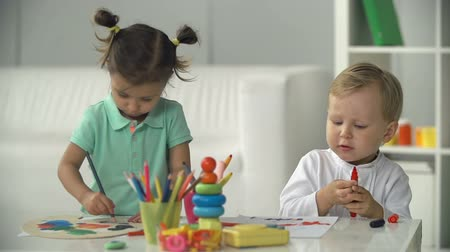 çizim : Two charming toddlers absorbed in painting and showing their pictures to each other