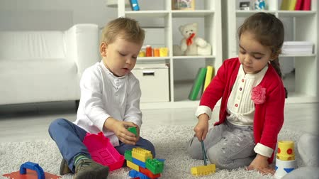 etkinlik : Boy and girl playing on the nursery floor constructing tinker toys