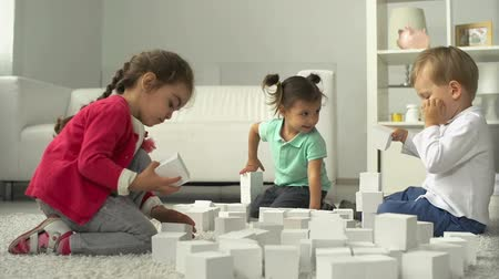 Three little friends playing with building blocks