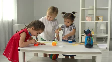 гуашь : Three toddlers drawing with paint on one huge canvas Стоковые видеозаписи
